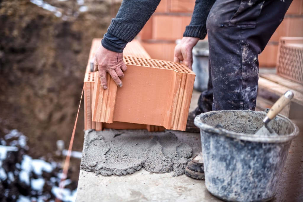 36552639 - construction site of new house, worker building the brick wall with trowel, cement and mortar